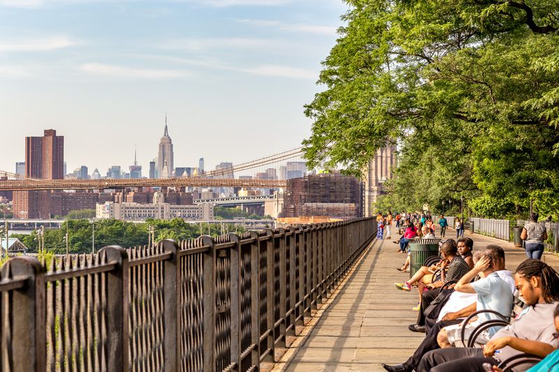 People sit on benches on a walkway with a long, wrought-iron railing. The New York City skyline is visible in the background.