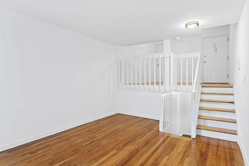 A bedroom with hardwood floors, white walls, and a staircase that leads to the entrance.
