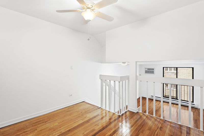 A bedroom section with a white staircase, hardwood floors, and white walls.