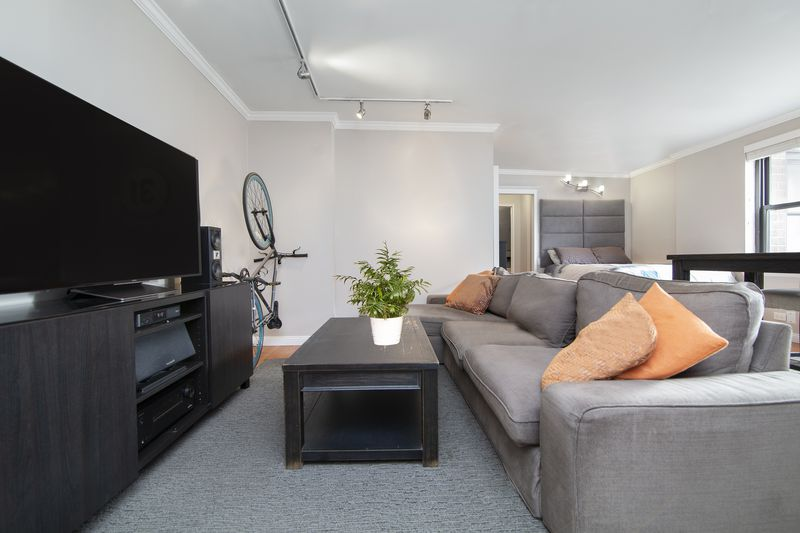 A living room area with a light grey couch and a large TV.
