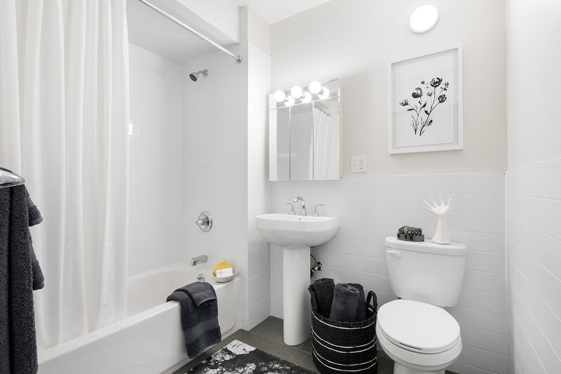 A bathroom with black floor tiles and white walls.