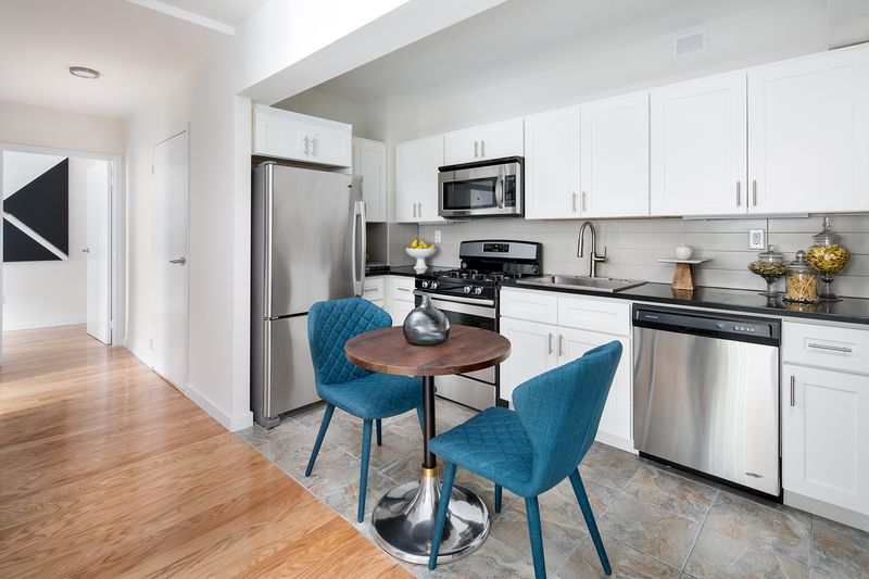 A kitchen area with white cabinetry and a round, wooden table with two blue chairs.