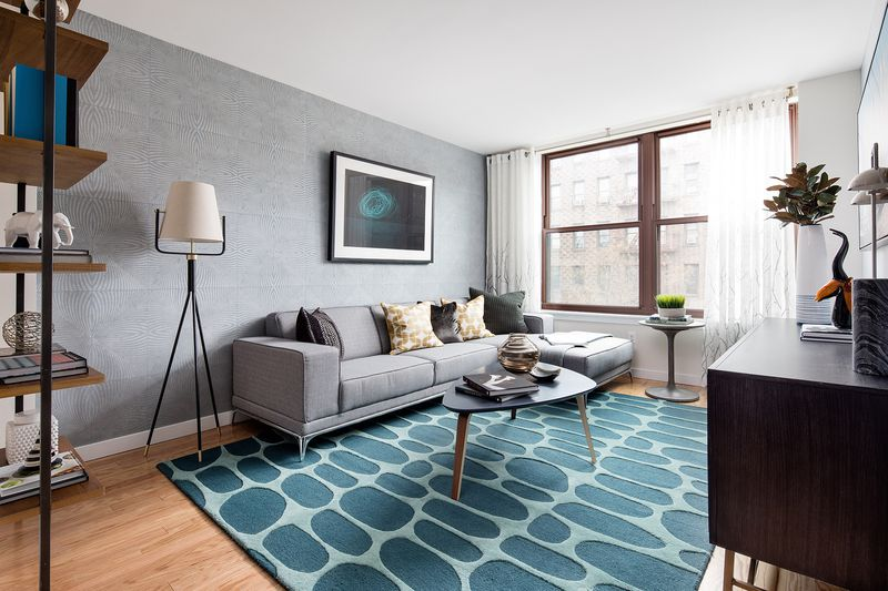A living room area with a blue rug, a light grey couch, a small table, and a tall lamp next to it.