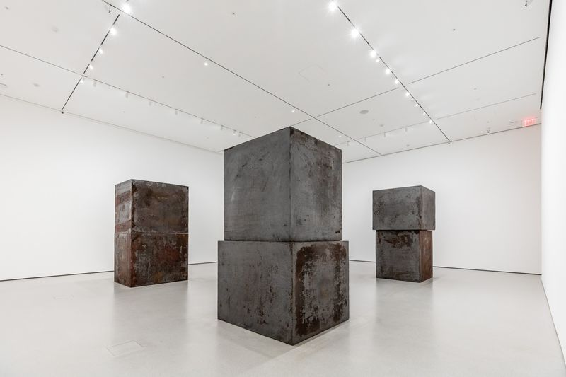 An installation in a gallery with large steel boxes stacked on top of one another.