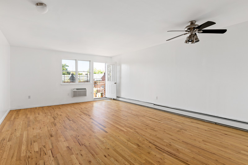 A large bedroom with hardwood floors, a ceiling fan, white walls, and a door that leads to a terrace.