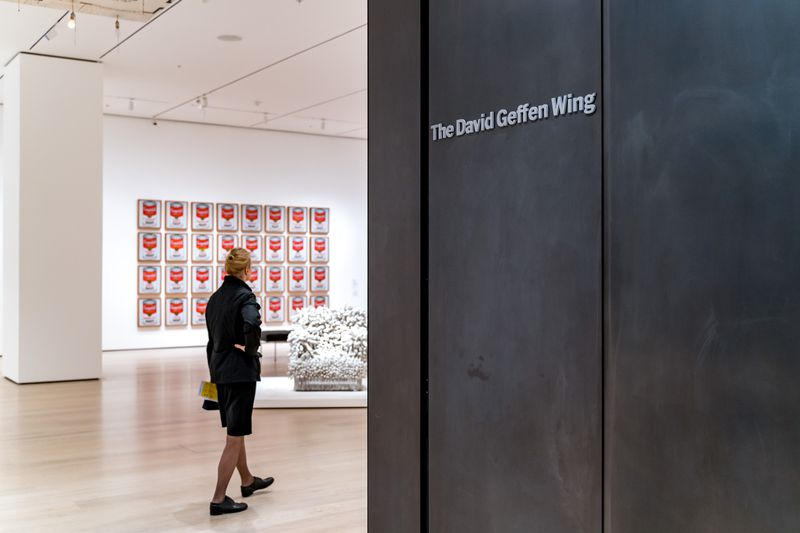 A view into a gallery with paintings of Campbell's soup cans on the wall, and a sculpture in the room.