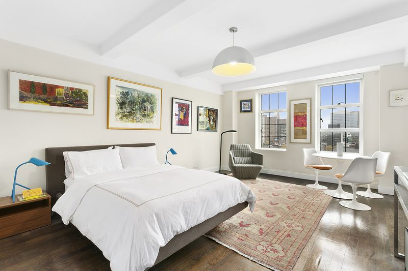 A bedroom with a large bed, a rug, hardwood floors, two large windows, and a round white table with chairs.