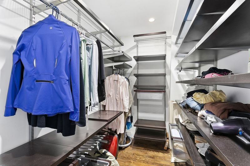 A walk-in closet with several pieces of clothing hanging and on top of shelves.