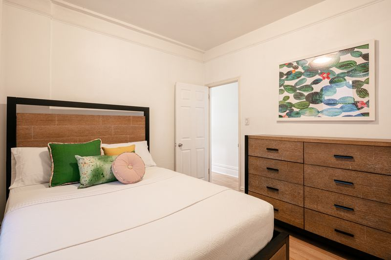 A bedroom with a medium-sized bed, white walls, hardwood floors, and a wood cabinet.
