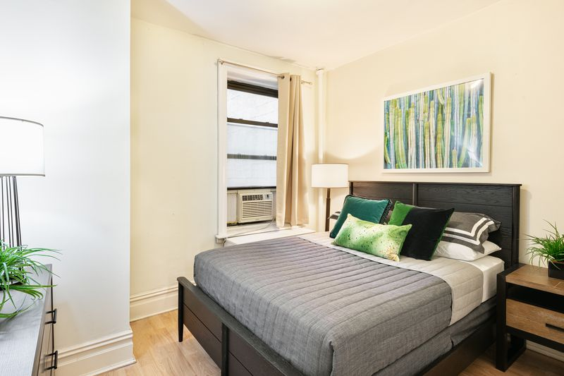 A bedroom with a large bed, hardwood floors, and a small window.