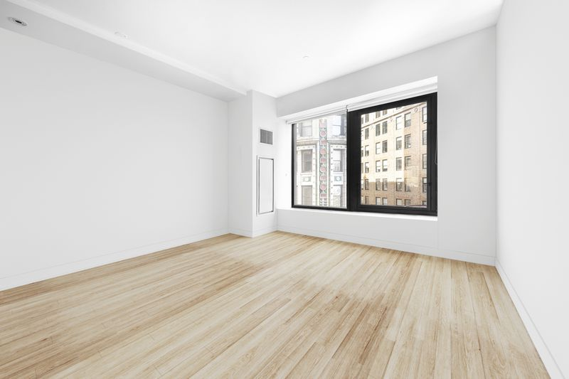 A bedroom with hardwood floors, white walls, and a large window.