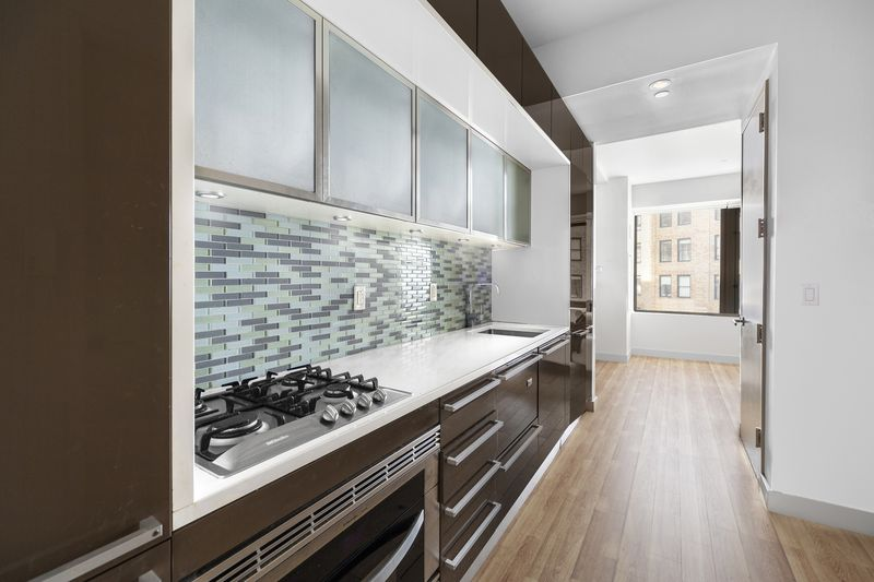 A kitchen with wood cabinetry and blue tiles on the wall.