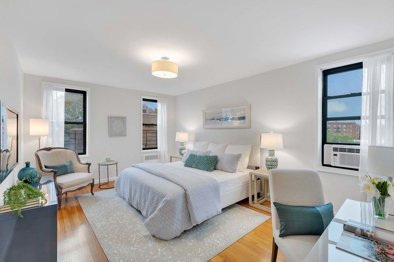 A bedroom with hardwood floors, white walls, a medium-sized bed, and a light grey rug.