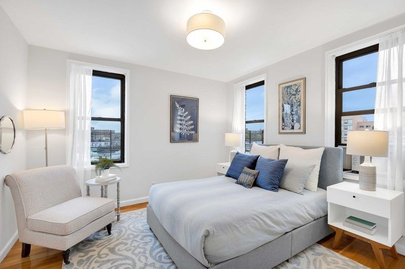 A bedroom with a medium-sized bed, a rug, a beige chair, three windows, and white walls.