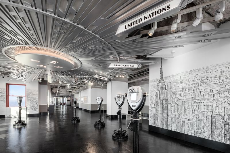 A floor with Art Deco-style ceilings, several binoculars, and walls covered in a black and white drawing.