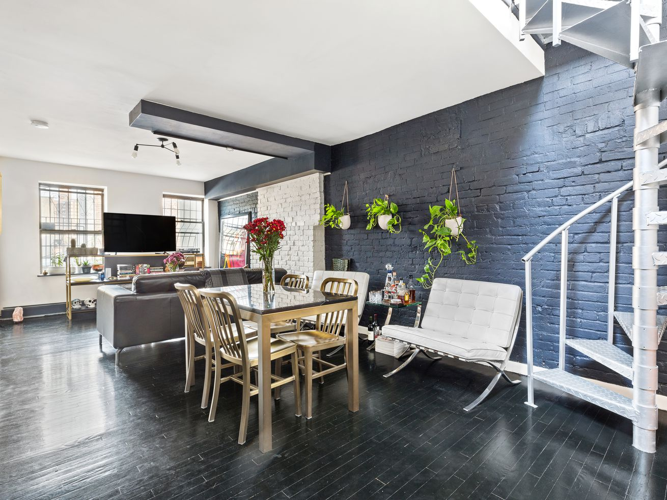 A living and dining areas with a table, several seating areas, planters, exposed brick, and a spiral staircase.