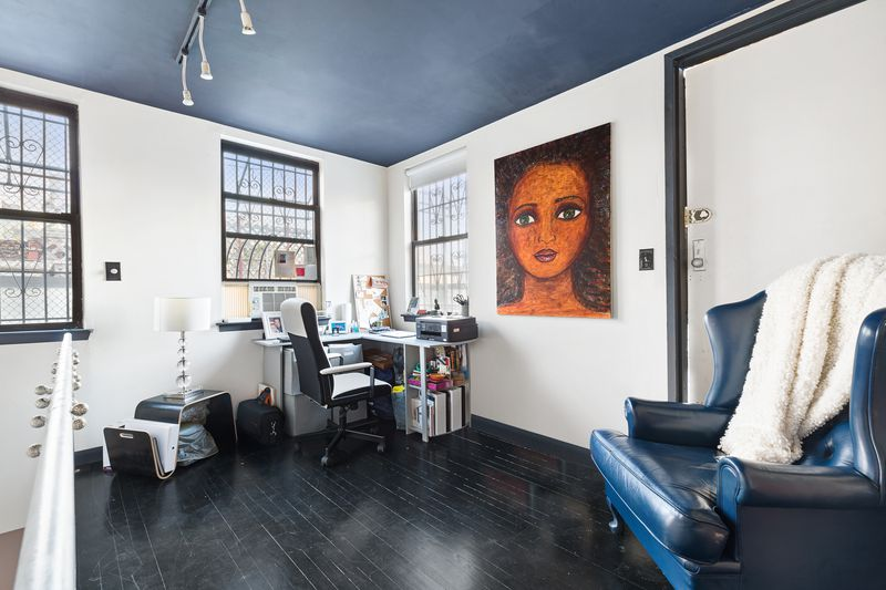 A den area with hardwood floors, several windows, a desk, a blue leather couch, and a painting hanging on the wall.