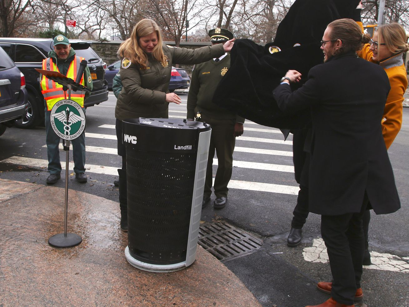 Several individuals stand around a black and grey trash can in a street corner.