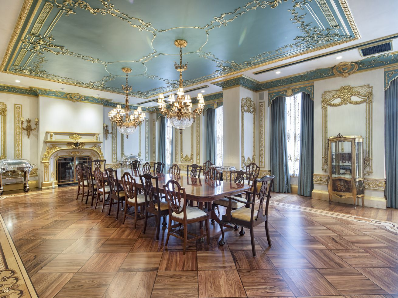 A dining room with hardwood floors, a large wooden table with chairs, large windows with blue curtains, two chandeliers, and a wood-burning fireplace.