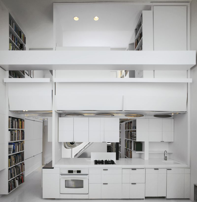 A duplex unit with white cabinetry, floors, and walls, and several built-in bookshelves.
