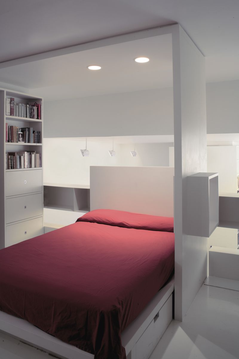 A small bed inside a white square-like structure with red sheets and built-in book shelves next to it.