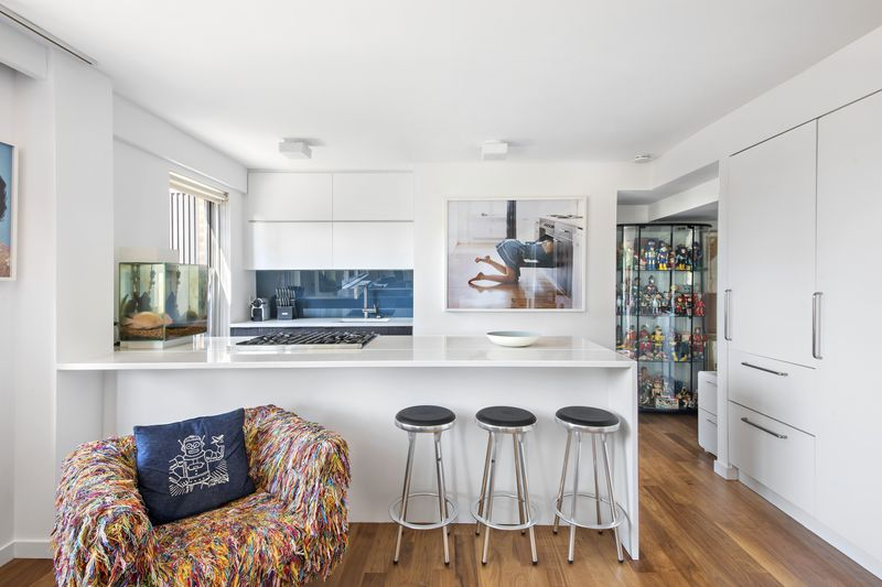 A kitchen with white cabinetry, a large island with high-top chairs, and a colorful couch.