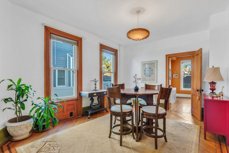 A dining room with a small table surrounded by four chairs. There are two windows. A door leads to another room.