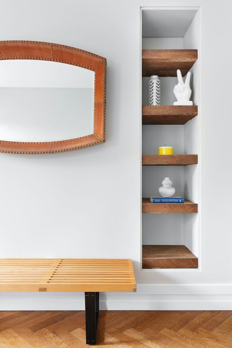 A wall with built-in wooden shelving.
