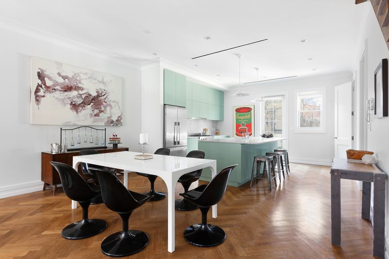 An open room with wood floors and white walls. There is a white table with six black chairs in the foreground. A kitchen with light green cabinets and a white counter is in the background.