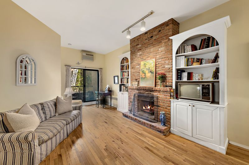 A living room area with a couch, yellow walls, white built-ins, and a wood-burning fireplace.