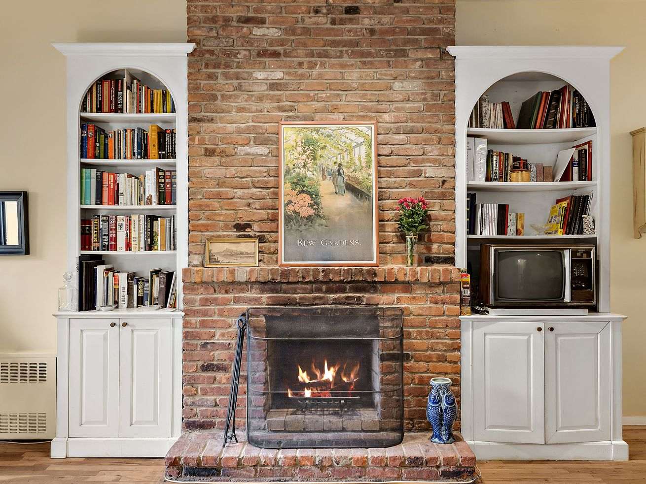 A wood-burning fireplace surrounded by a brick wall and two white built-in bookshelves.