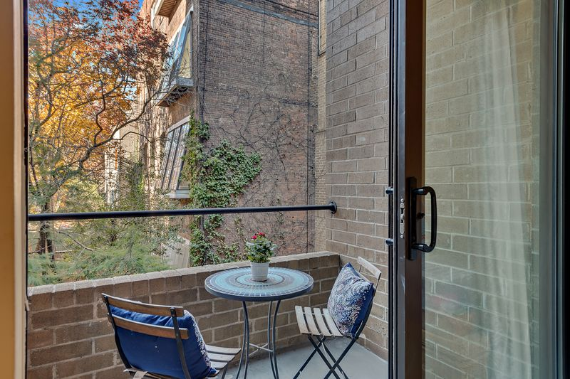 A balcony with a small table, two chairs, and brick walls.