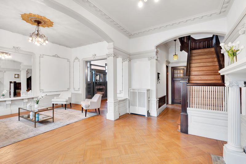 A foyer with hardwood floors, a wooden staircase, and Ionic columns.