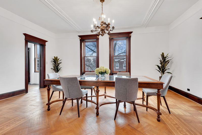 A dining area with hardwood floors, a large table, and a chandelier on top.