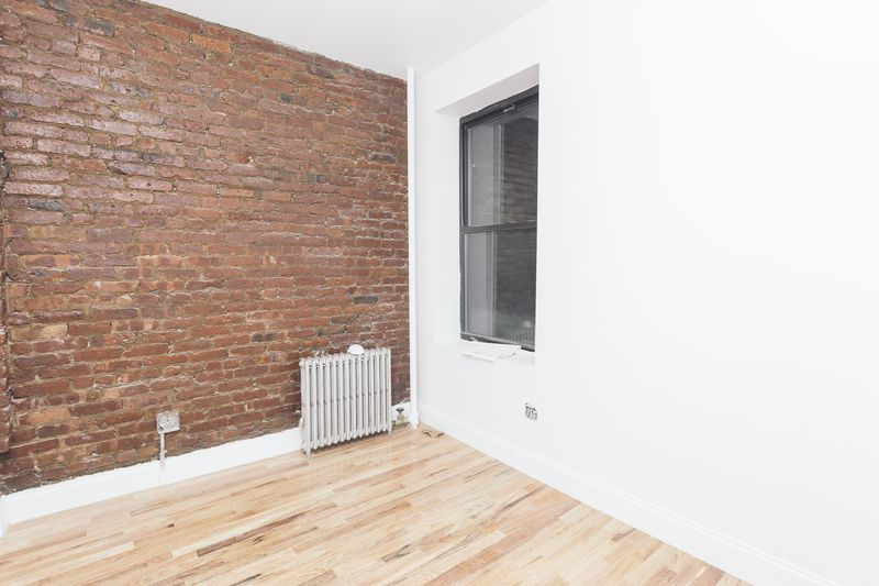 A bedroom with exposed brick, a window, and white walls.