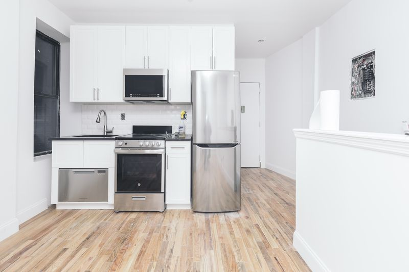 An open kitchen with white cabinetry and hardwood floors.