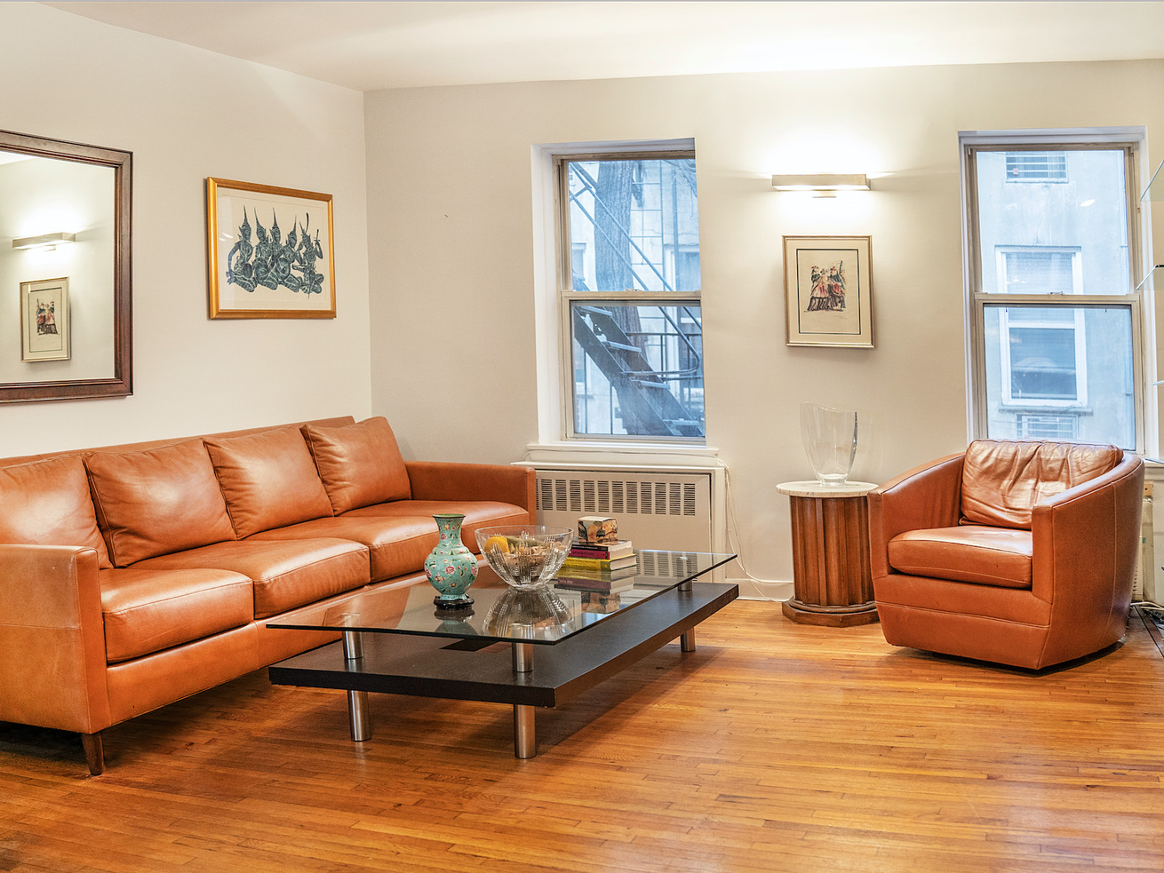 A living area with hardwood floors, two windows, a brown leather couch, and white exposed brick.