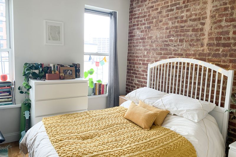 A bedroom with two windows, exposed brick, and a medium-sized bed.
