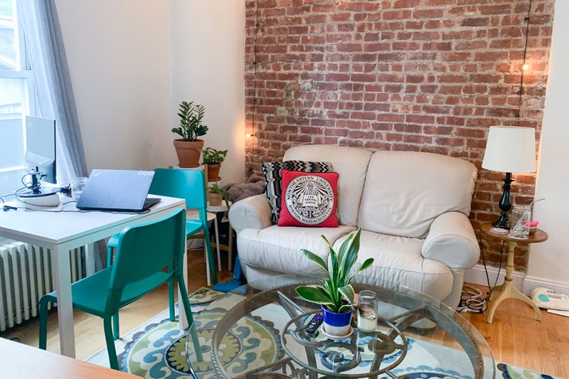 A living area with exposed brick, hardwood floors, and a small white couch.