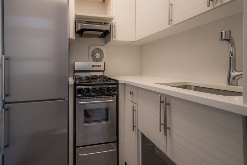 A kitchen with wood cabinetry and a small stove.