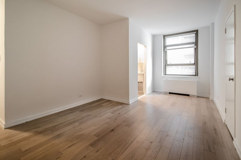 A living area with hardwood floors, a window, and white walls.