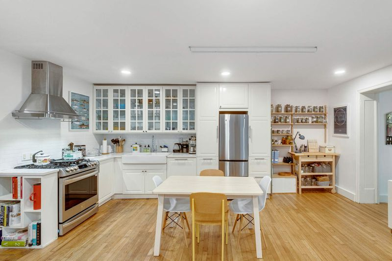 An open kitchen with white cabinetry and a small white table with four chairs.