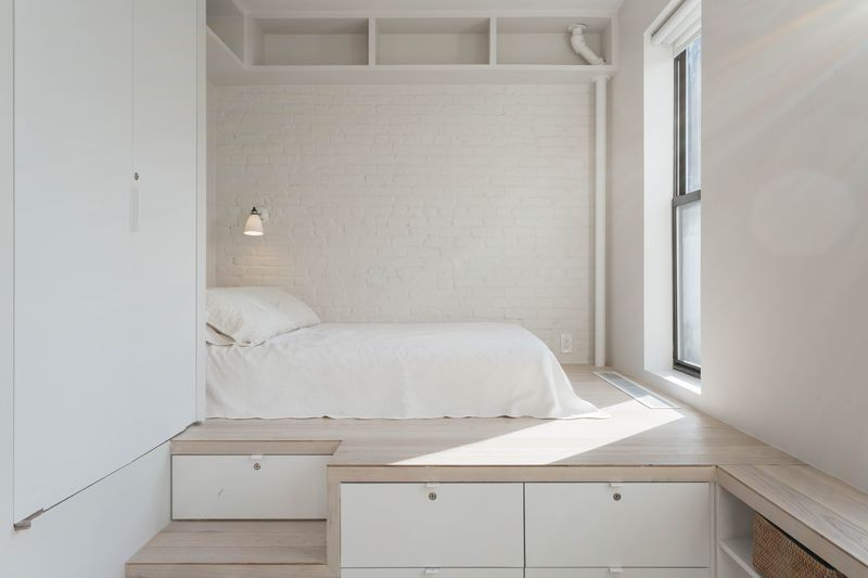 An alcove in a studio with a small bed, white exposed brick, pale oak floors, and a window.