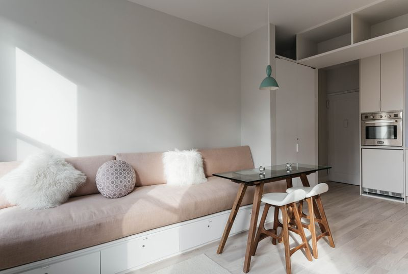 A living area with pale oak floors, a dusty pink couch, and a glass coffee table.