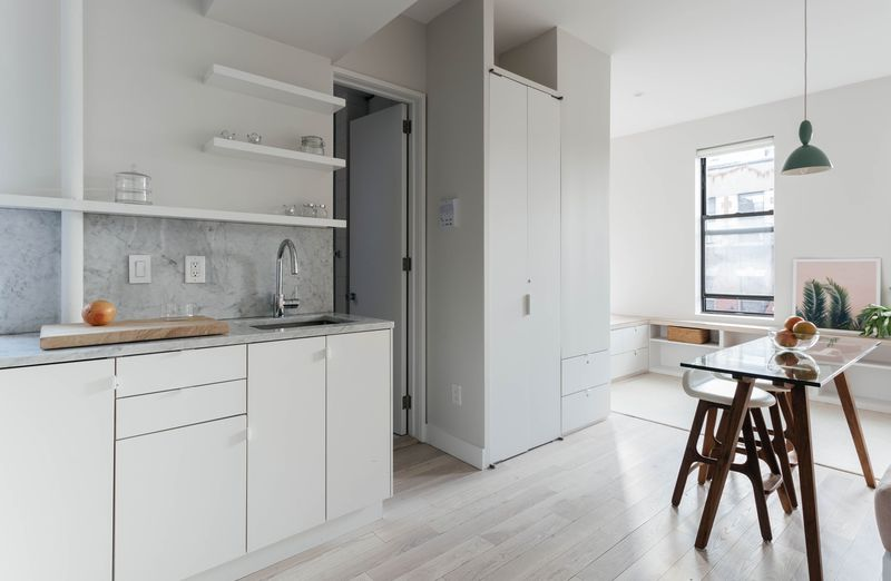 A kitchen with pale oak floors and white cabinetry.
