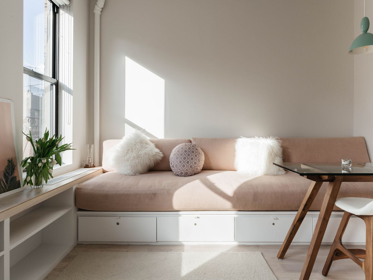 A dusty pink couch in a living room with a window and a glass coffee table.