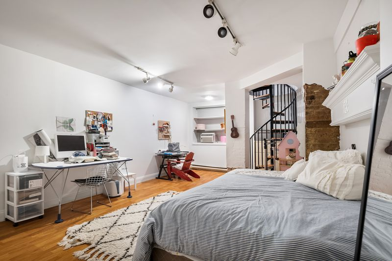 A bedroom with exposed brick, a medium-sized bed, a desk with a computer, and white walls.