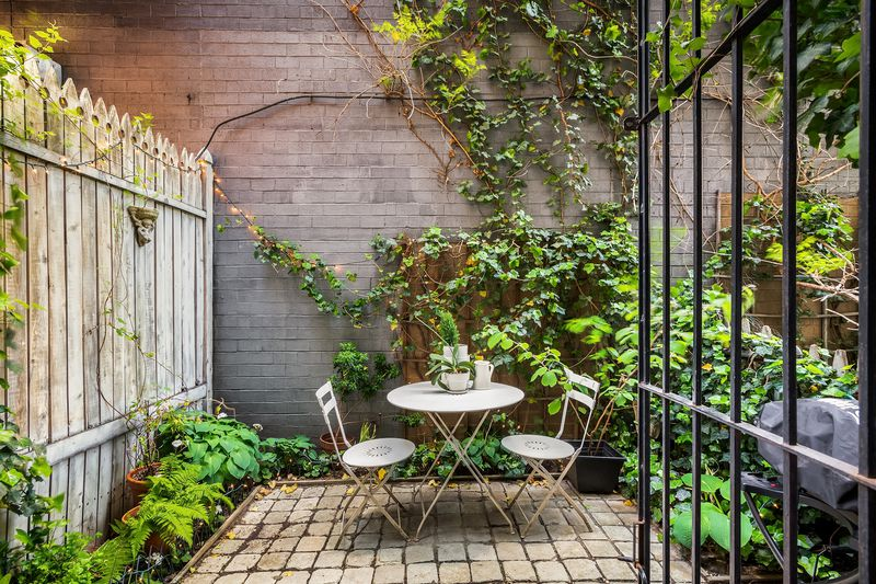 A small patio with a round table and two chairs, ivy-covered wood fencing, and brick tiles.
