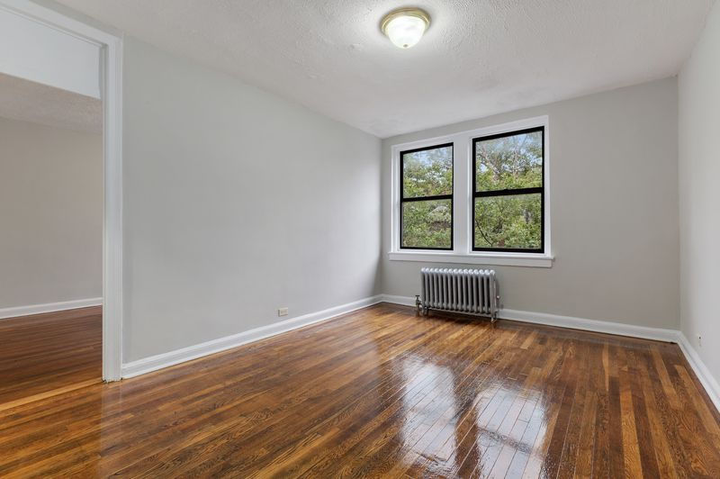 A room with hardwood floors, two windows, and base moldings.