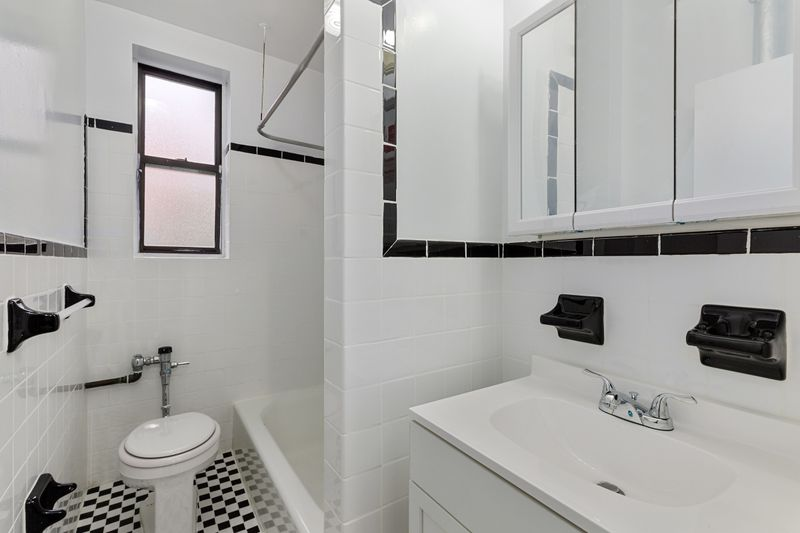 A bathroom with white and black tiles and a small window.